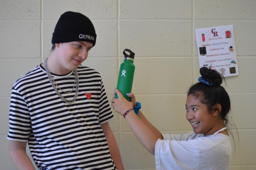 A VSCO girl making an E-Boy view her emerald hydro-flask while showing their school spirit for Spirit Week.